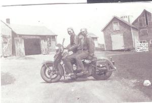 Dad (front) and Uncle Edward. Tool shed on left, grain house on right, milk house in middle.