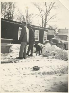 Dad, Uncle Edward, and Wolfy outside our basement home. This is not our big snow pile.